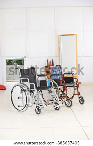 Two empty wheelchairs as symbol for euthanasia in nursing home - stock photo
