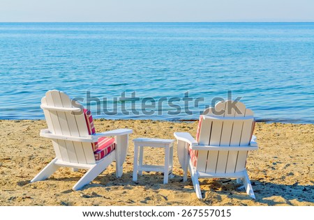 Two empty white armchairs on the beach beside the turquoise sea - stock photo