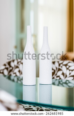 Two empty white vases with cracked design on the glass table - stock photo