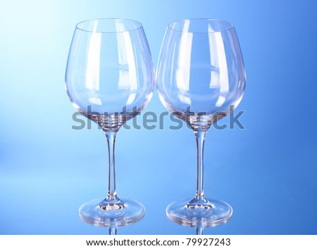 Two empty wine glasses on blue background - stock photo