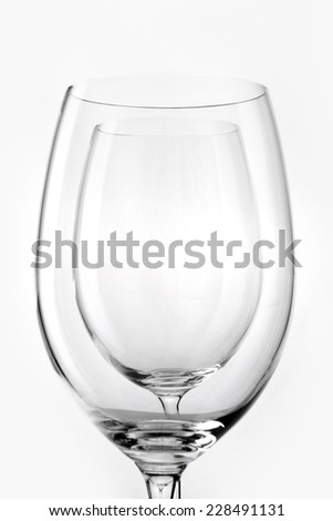 Two empty wine glasses overlapped close up isolated white. - stock photo