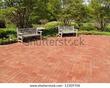two empty wood benches by a red brick patio in a garden - stock photo