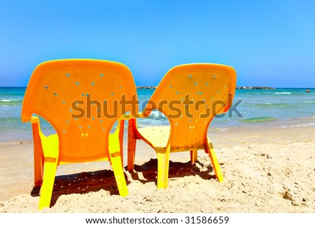 Two empty yellow chairs on beach close up - stock photo