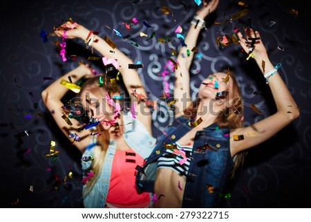 Two energetic girls dancing in confetti falling - stock photo