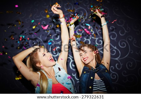 Two energetic girls dancing in night club - stock photo