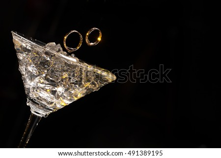 Two engagement rings in the glass on a studio background