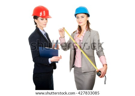 Two engineer businesswomen with tape measure. - stock photo