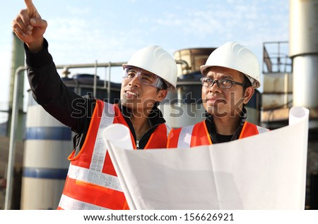 two engineer checking a drawing on location - stock photo