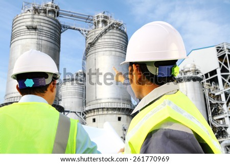 Two engineer oil gas refinery discussion under storage tank industry - stock photo