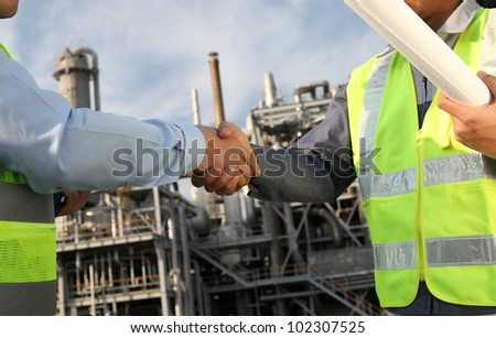 two engineer oil industry closing a deal in front of an large oil refinery - stock photo