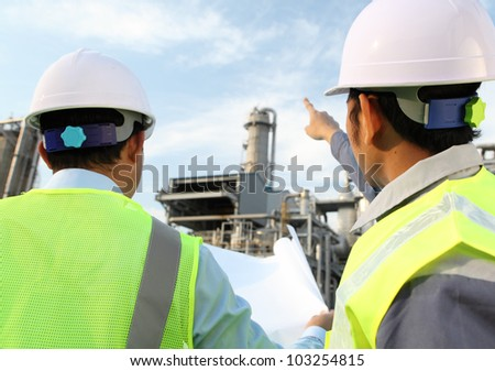 two engineer oil industry discussing a new project with large oil refinery background - stock photo