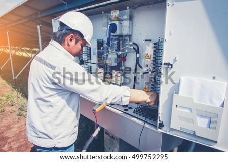 two engineer working on checking and maintenance equipment at green energy solar power plant: checking status inverter
