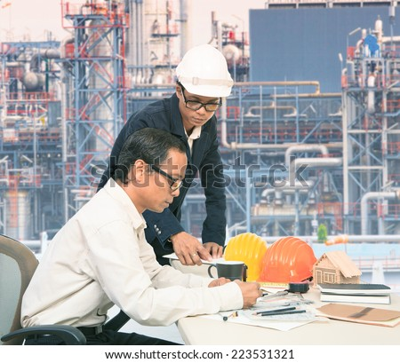 two engineer working on table against exterior of oil refinery plant use for petrochemical industry topic and related - stock photo