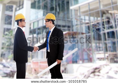 Two engineers closing a deal by handshake in front of a building site - stock photo