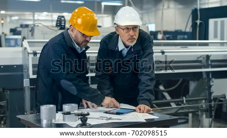 Two engineers discuss a blueprint while checking information on a tablet computer in a factory.