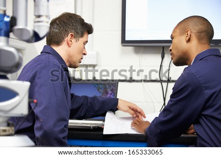 Two Engineers Discussing Plans With CMM Arm In Foreground - stock photo