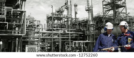 two engineers in front of large oil refinery, panoramic idea - stock photo