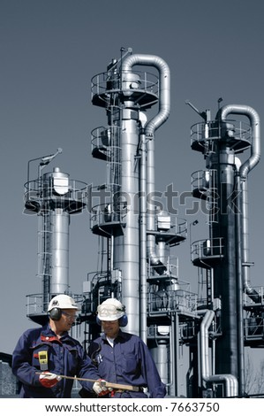 two engineers in hard-hats, standing in front of oil and gas refinery - stock photo