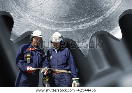 two engineers in hard-hats with giant machinery, gears, in background, - stock photo