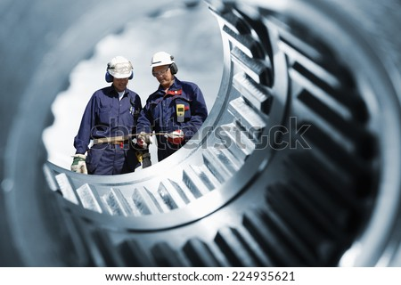 two engineers seen through a large cogwheels gear shaft, metal industry - stock photo