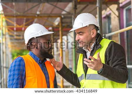 Two engineers wearing hardhat and safety jacket discussing on construction site - stock photo