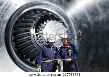 two engineers, workers with giant cogwheels axle in background - stock photo