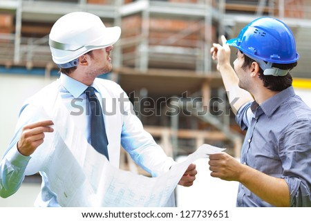Two engineers working in a construction site - stock photo