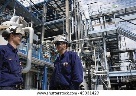 two engineers working inside oil and gas refinery - stock photo