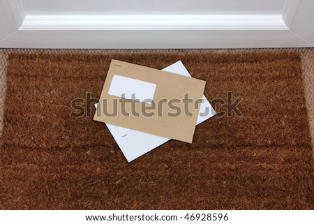 Two envelopes on a doormat, blank window to add your own name and address details. - stock photo