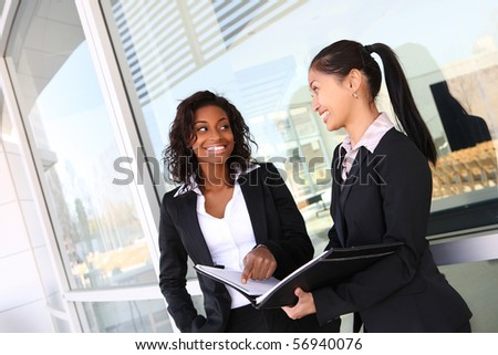 Two ethnic asian and african business women team at office building - stock photo