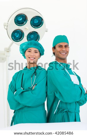 Two ethnic surgeons smiling at the camera - stock photo