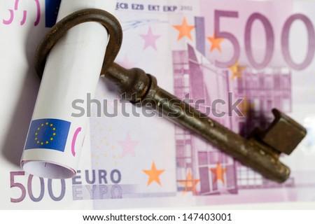 two 500 Euro banknotes an antique key - stock photo