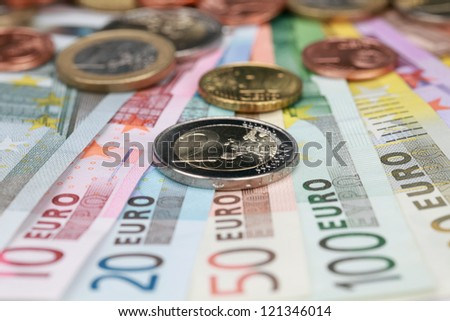 Two Euro coin on Euro banknotes forming a money background