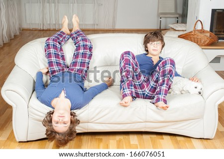Two European boy, brother, in pajamas, indulge on the couch, next to a small white dog - stock photo