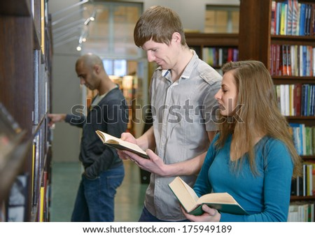 Two european students, beautiful girl and handsome boy, standing by a bookshelf in a library and reading books, another student, a middle eastern boy, on background.