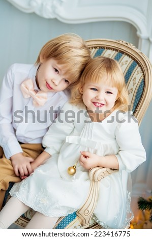 Two evening dressed children are sitting on a chair - stock photo