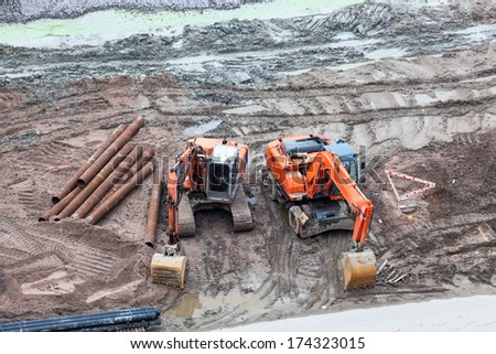 Two excavator at dirty construction site - stock photo