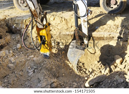 Two excavators in action to perform an excavation in rock. One with hydraulic hammer destroys the rock and the other with the machine loads a truck - stock photo