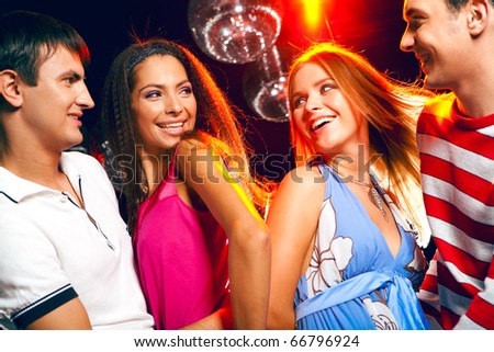 Two excited couples looking at each other with smiles during disco - stock photo
