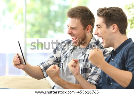 Two excited friends or roommates watching tv on line in a tablet sitting on a couch in the living room at home - stock photo