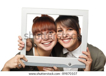 Two excited girls looking through the old fashioned computer screen, isolated on white background - stock photo