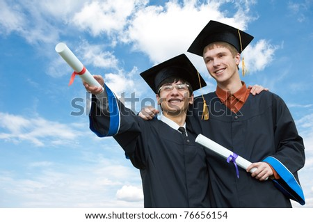 two excited graduate students in gown with risen hands holding diploma over blue sky - stock photo