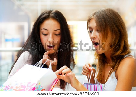 Two excited shopping woman gossip together inside shopping mall. Horizontal Shot - stock photo