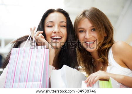 Two excited shopping woman together inside shopping mall, surprised about low prices and sales before christmas and boxing day. Horizontal Shot - stock photo