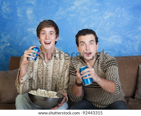 Two excited young Caucasian men with soda can and bowl of popcorn - stock photo