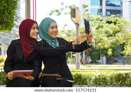 Two executive using tablet touchscreen outdoor  - stock photo