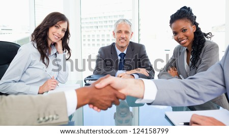 Two executives and their director smiling while looking at colleagues shaking hands - stock photo
