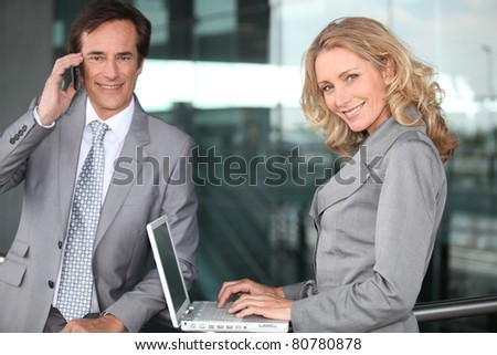 Two executives working outside an office building - stock photo