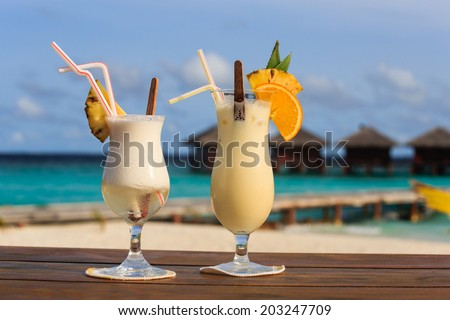 Two exotic cocktails on tropical beach - stock photo