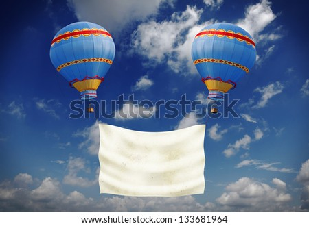 Two exotic colorful hot air balloon carrying a blank banner against a blue cloudy sky.
